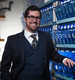 Portrait of smiling Beck Wehrle in a three piece suit with a lizard tie, zebrafish tanks in background